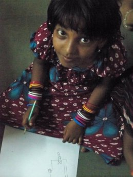 small girl in India looks up from her drawing